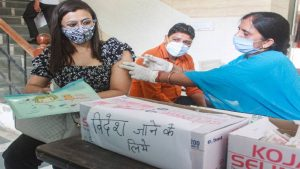 A beneficiary receives a dose of COVID-19 vaccine during a vaccination camp for students and citizens undertaking international travel in Gurugram.